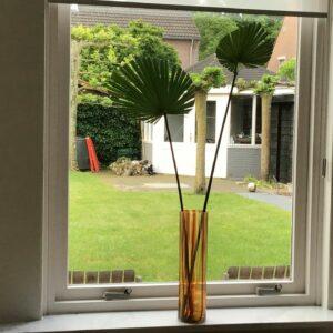 Hoge glazen vaas met palmbladeren